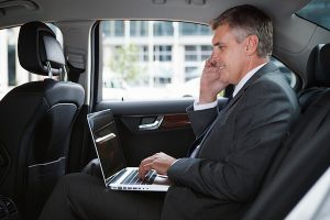 Divine Strategies - Businessman in car with cellphone and laptop